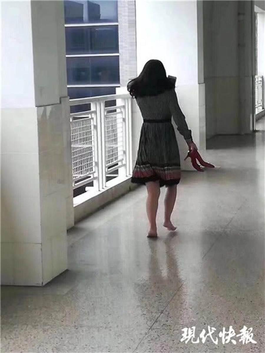 一名家長脫高跟鞋赤腳走上四樓給兒送筆盒照片,感動網友。(取自《現代快報》)
