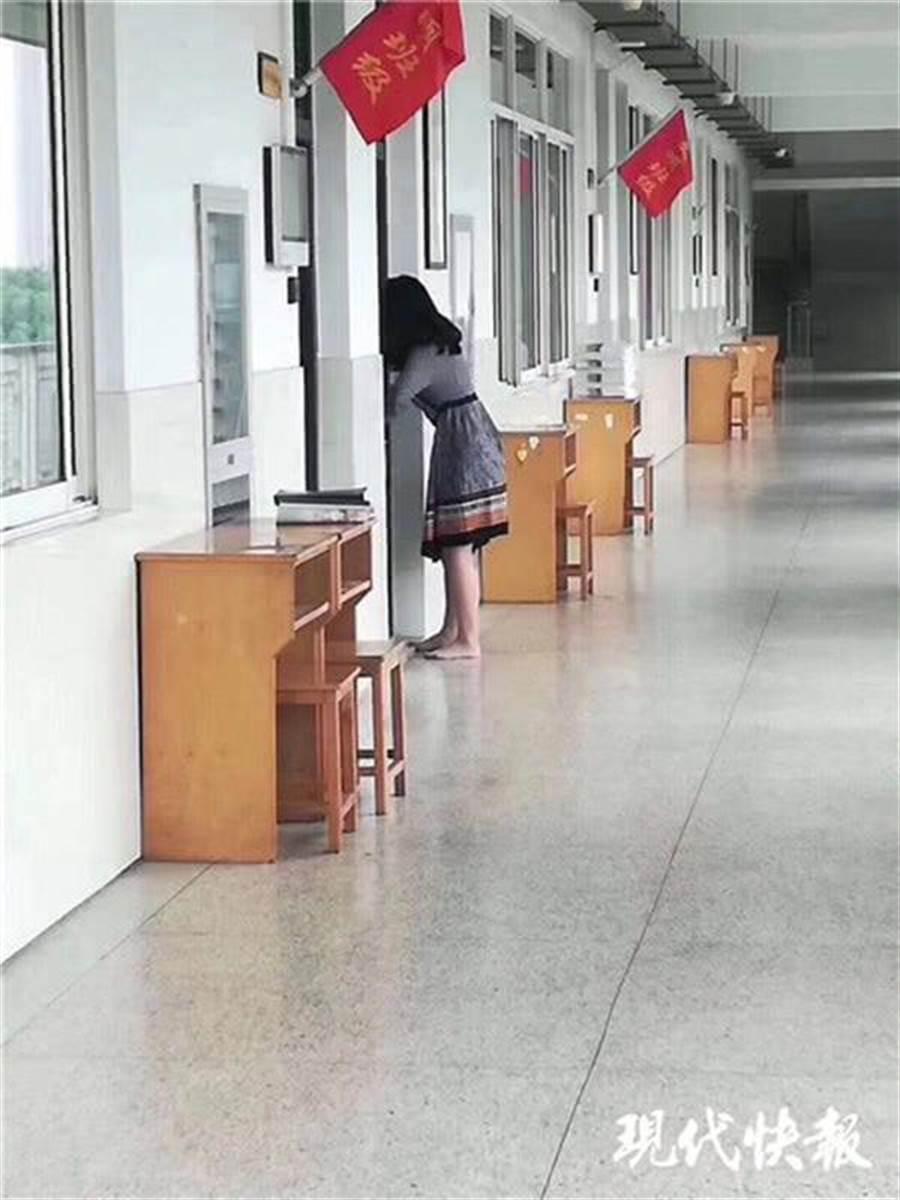 擔心打擾上課,她脫了高跟鞋赤腳在教室外行走。  (圖取自《現代快報》)