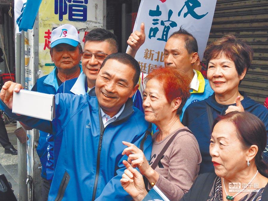 國民黨新北市長參選人侯友宜(前左)18日上午到永和區民治市場掃街拜票,與支持者自拍。(葉書宏攝)