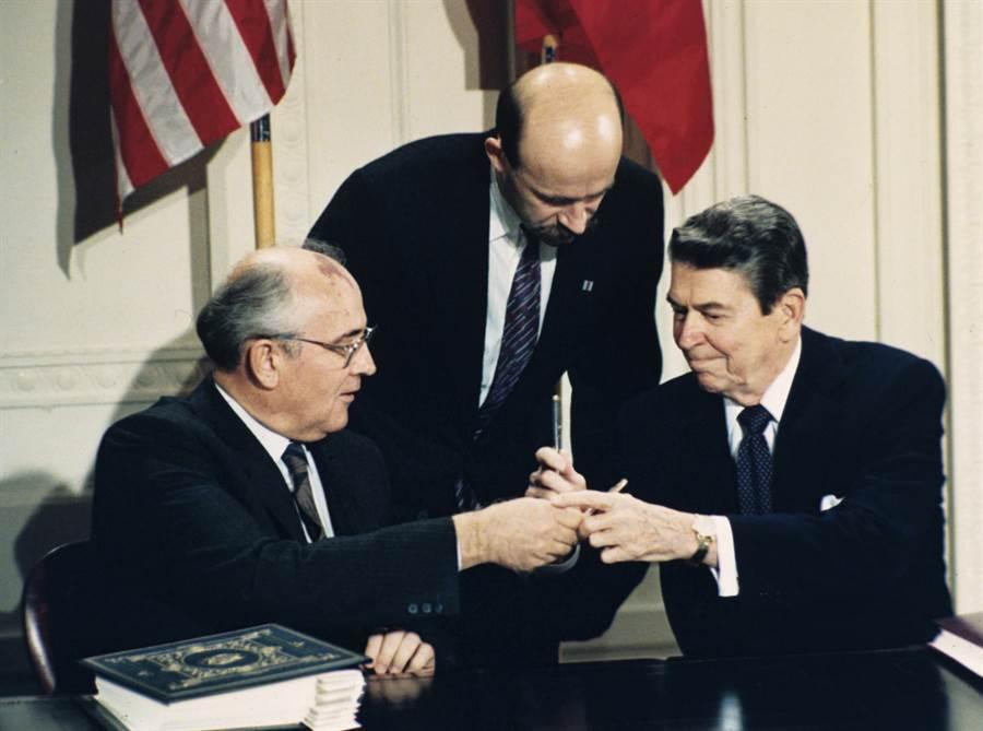 美國前總統雷根(右)與前蘇聯領導人戈巴契夫(左)於1987年12月在白宮簽署《中程導彈條約》後,相互交換簽約用的鋼筆。站立中間的是俄國翻譯帕拉成科。(圖/美聯社)