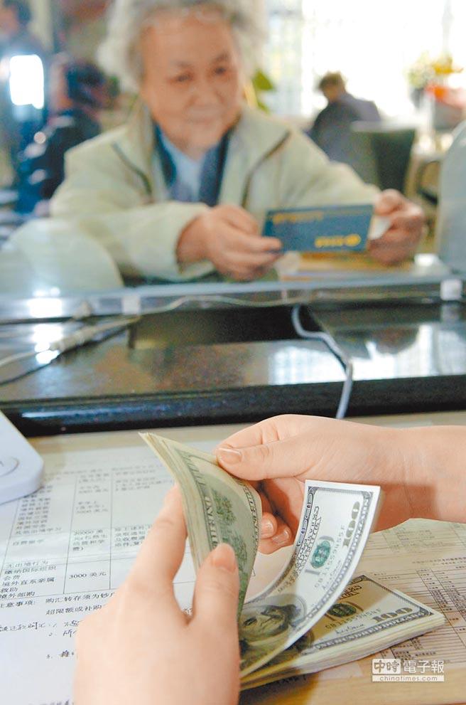 強勢美元,引爆銀行間的搶錢大戰。圖為客戶辦理美元存款業務。(新華社)