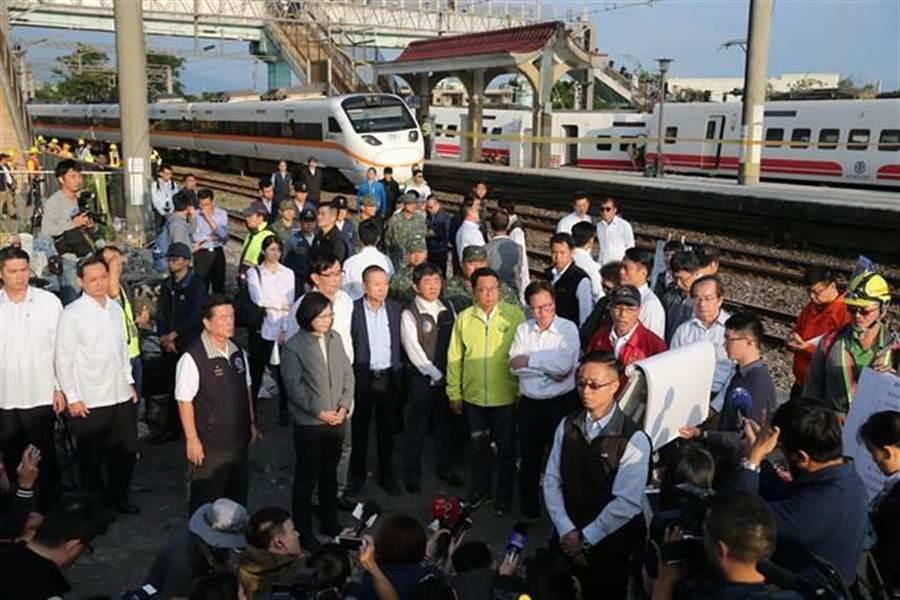 蔡英文總統(左四)22日前往宜蘭縣新馬站事故現場勘災,單線雙向通行的西線一部太魯閣號傾斜式列車正巧經過,後方為事故車普悠瑪號。(資料照片 黃世麒攝)