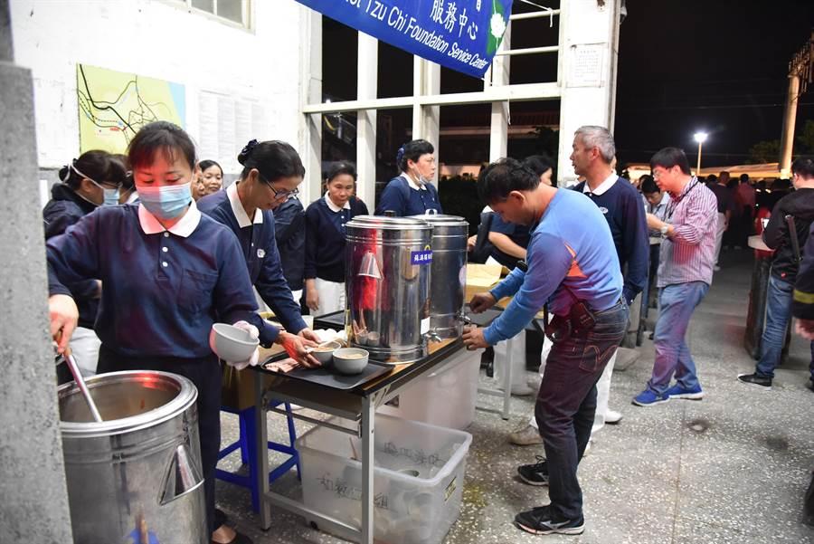 慈濟志工在宜蘭縣蘇澳鎮新馬車站成立服務中心,提供熱薑茶、熱食、礦泉水、福慧珍粥、乾糧給工作人員。(圖/慈濟基金會提供)