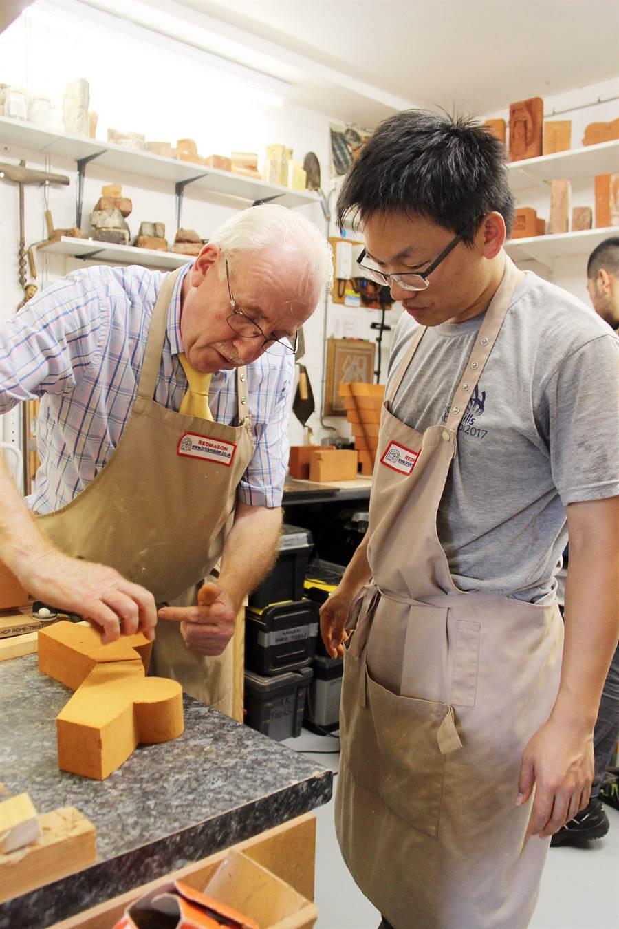 國際技能競賽砌磚職類優勝,台科大營建系周承誼,向英國砌磚專家Dr. Lynch學習英國傳統的砌磚工法及磚雕藝術。(台科大提供)