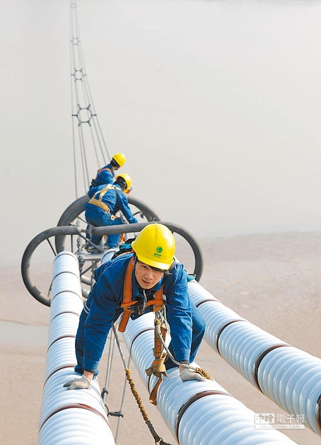 安徽電力公司員工對高壓直流輸電線路進行檢修。(新華社)