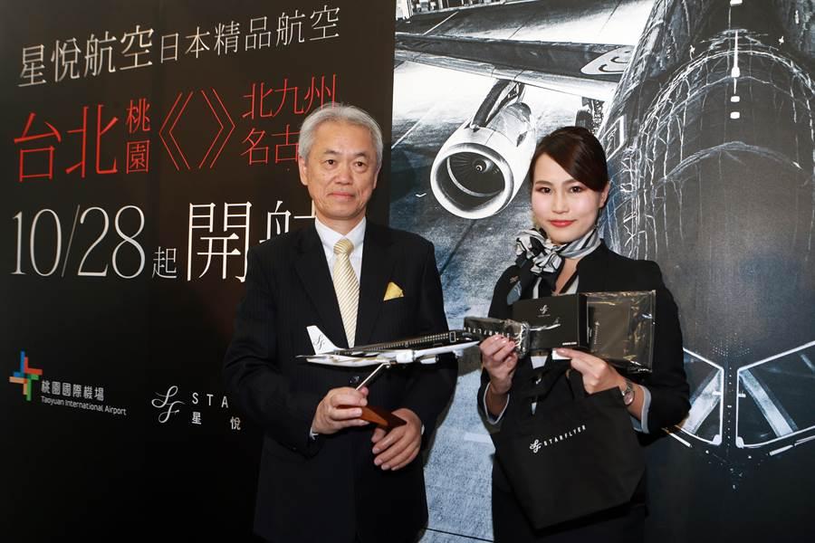 星悅航空台北支店長石山健二(左)與空服員展示首航飛機模式與首航禮品。(陳麒全攝)