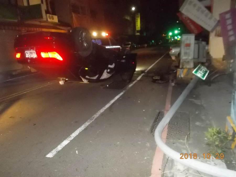 年輕男子駕駛BMW大七轎車年輕男子失控撞路燈桿及電箱後翻覆,愛車四輪朝天慘不忍睹。(陳淑芬翻攝)