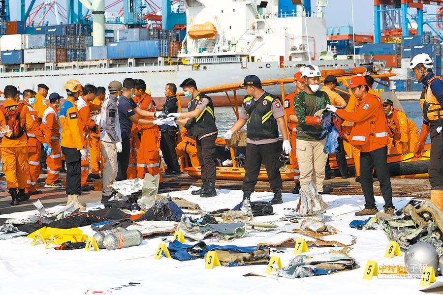 印尼獅航空難發生後,救援人員在飛機墜海的爪哇海水域,打撈起飛機殘骸和乘客的行李物件。(法新社)