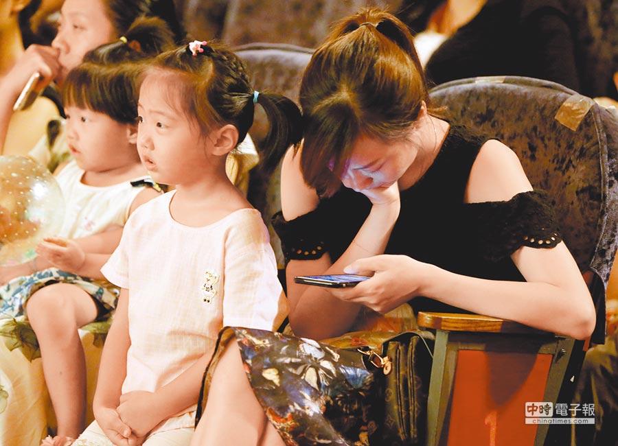 湖北襄陽的低頭族父母,忙著玩手機。(CFP)