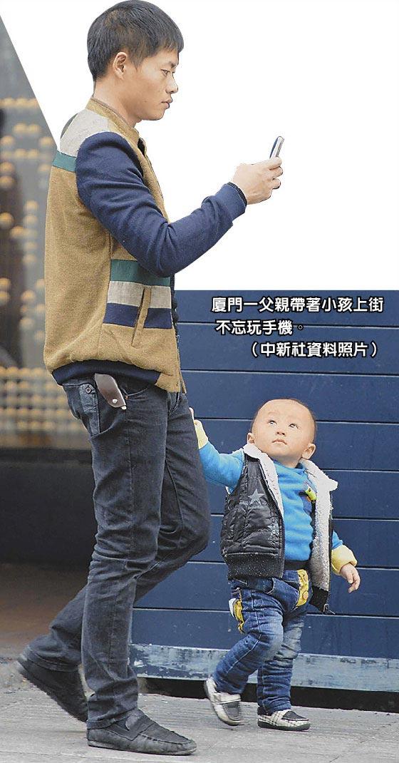 廈門一父親帶著小孩上街不忘玩手機。(中新社資料照片)