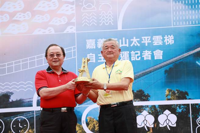 阿管處處長馬惠達(左)將象徵性的太平雲梯雕塑交給太平合作社理事主席嚴清雅(右)。(張亦惠攝)