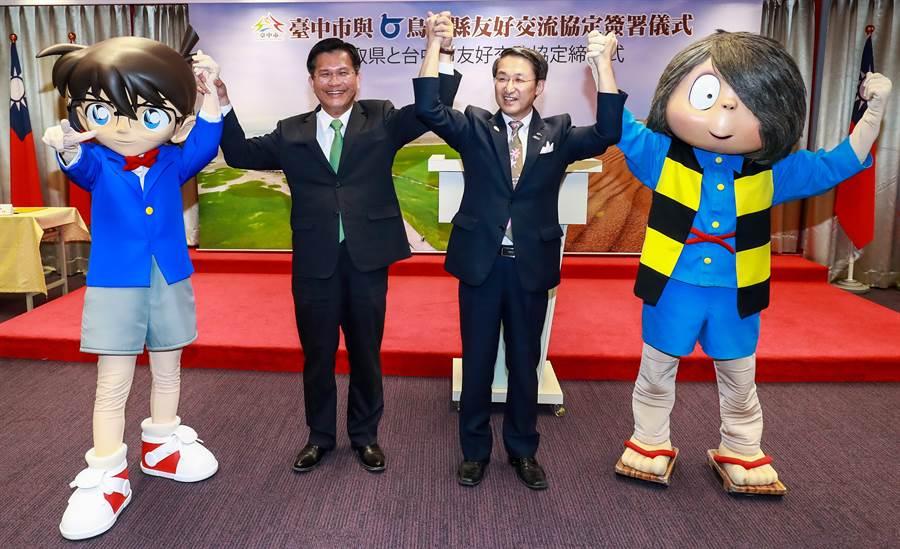 台中市長林佳龍(左)2日與鳥取縣知事平井伸治簽署友好交流協定,看到出自鳥取縣的《名偵探柯南》童心大發。(盧金足攝)