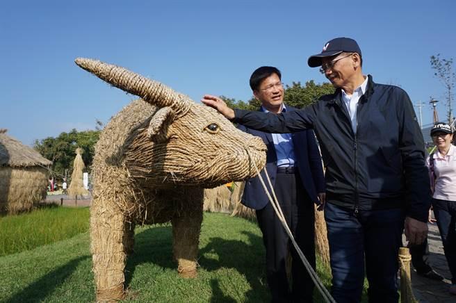 前行政院長游錫堃(右)在選前參訪台中花博,他看到稻草編成的水牛裝置藝術,忍不住上前撫摸牛頭,並為子弟兵林佳龍(左)加油打氣。(王文吉攝)