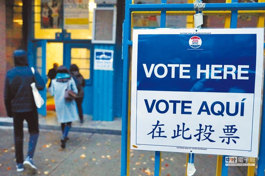 美國6日舉行期中選舉,紐約市曼哈頓民眾出門投票,投票所門口用中文、英文與西文寫著「在此投票」。(路透)