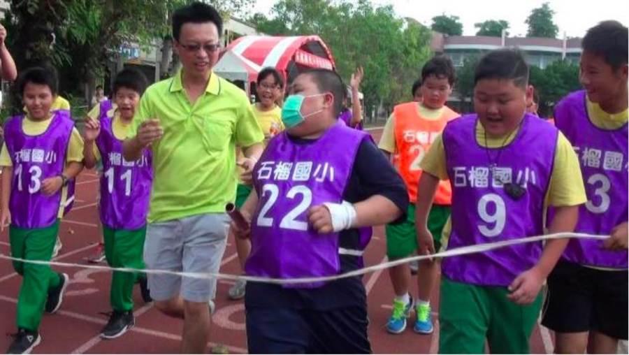 罹患血癌學生黃紹華(中)在師生陪同下,跑向大隊接力終點,完成他的心願。(周大觀基金會提供)