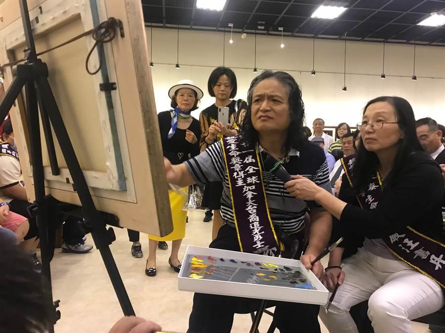 自幼罹患小兒麻痺症台裔加籍嚴榮宗(左),在中正紀念堂3樓四展廳展出畫展,他在現場創作以示紀念。(王思慧攝影)