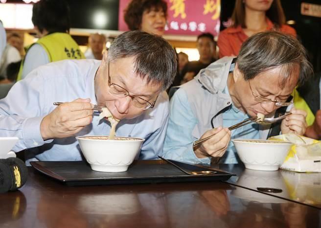 台北市長柯文哲(左)9日前往南門市場拜票並與競選總幹事小野(右)一同坐下來吃麵。(姚志平攝)