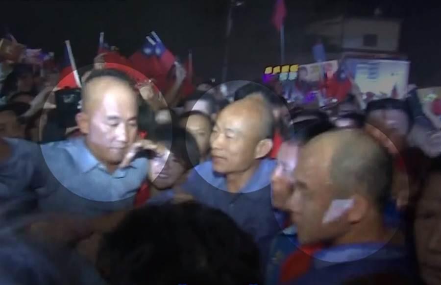 韓國瑜左右各有一名藍襯衫的光頭護衛隨行。(圖/中天新聞)