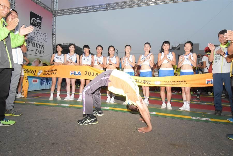 彰化縣長魏明谷在跑者起跑前秀出驚人好腰力,俐落下腰後再現「人體拱橋」,不久後俐落起身,引發陣陣歡呼。(謝瓊雲攝)