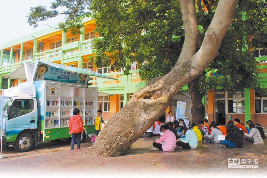 佛光山雲水書坊行動圖書館開到苗栗縣頭份國小,學生在校園內大樹下閱讀。(本報資料照片)