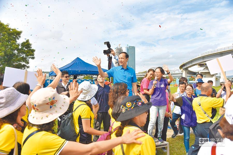 新北市國際志工日嘉年華活動10日在大台北都會公園舉行,由於新北市長朱立倫12月將卸任,志工們紛紛上前爭取合拍「畢業照」,為活動掀起另一波高潮。(譚宇哲翻攝)