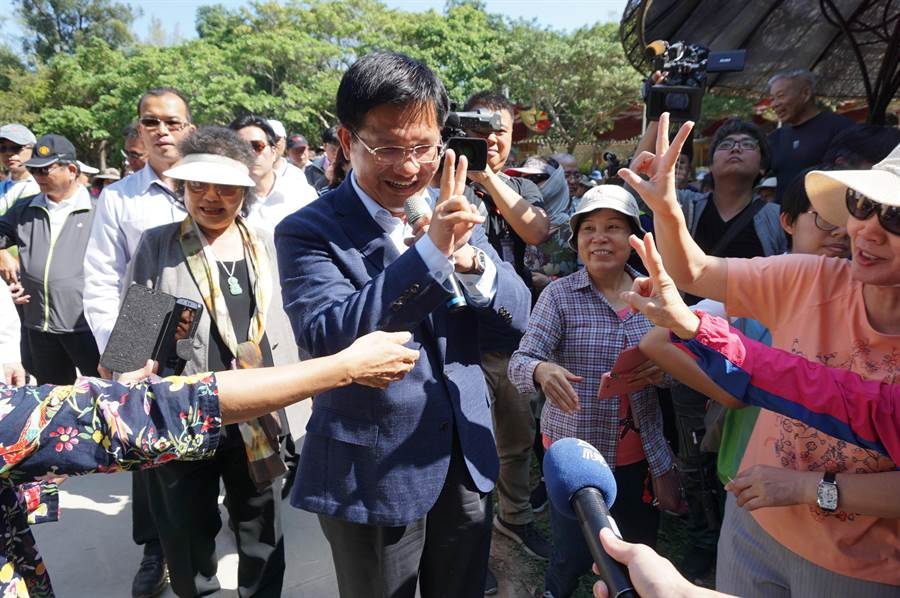 許多遊客搶著與「花媽」陳菊及林佳龍合影,支持者不忘比出「YA」手勢,力挺林佳龍連任。(王文吉攝)
