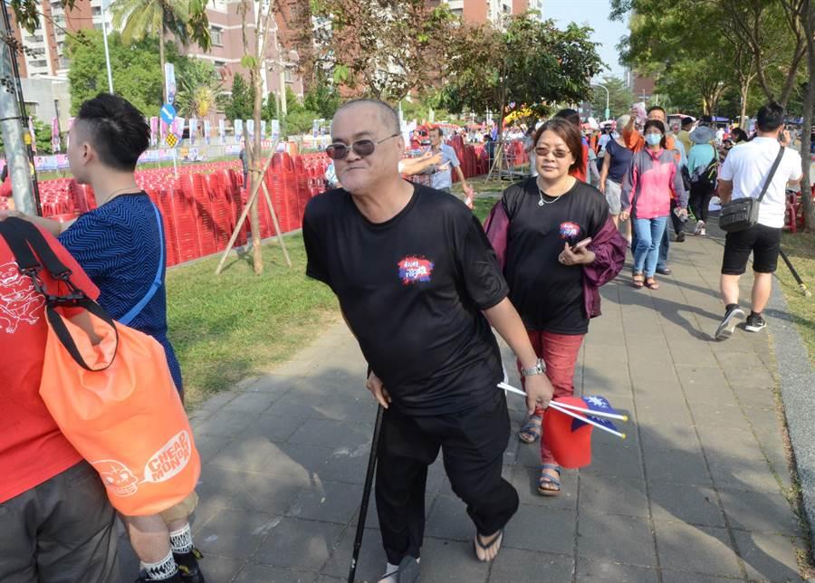 挺韓國瑜造勢晚會14日晚間將在高雄市岡山區河堤公園舉行,一名老伯拄著拐杖,另一手拿著國旗,賣力走進會場。(林瑞益攝)