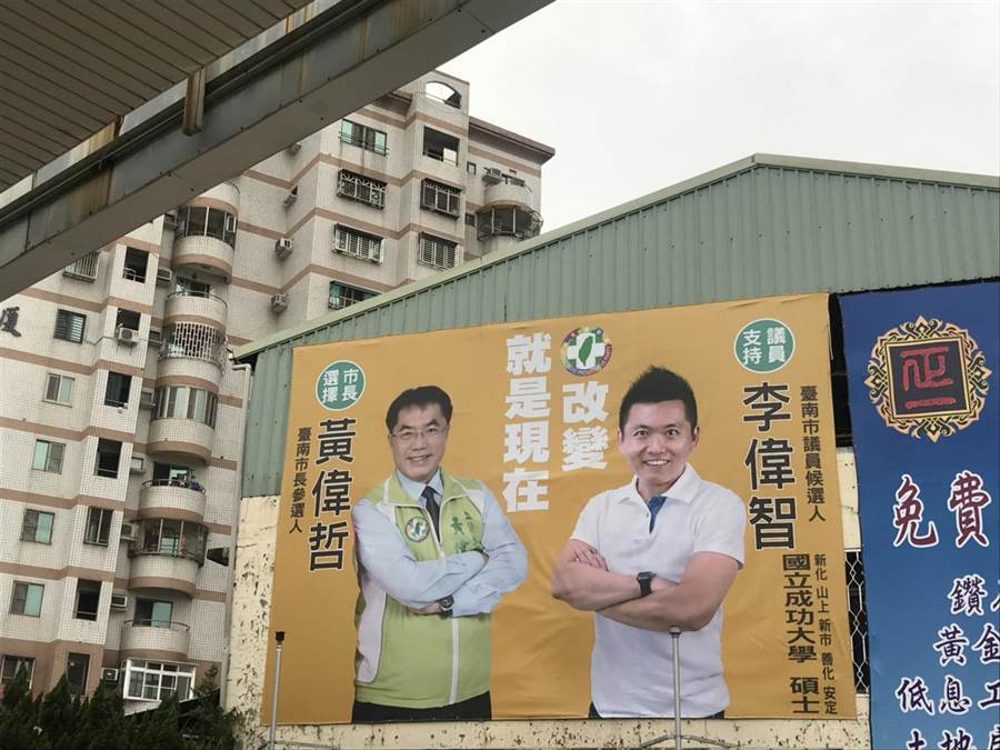 民進黨台南市議員候選人李偉智(右)與同黨台南市長候選人黃偉著折合掛看板。(李其樺攝)