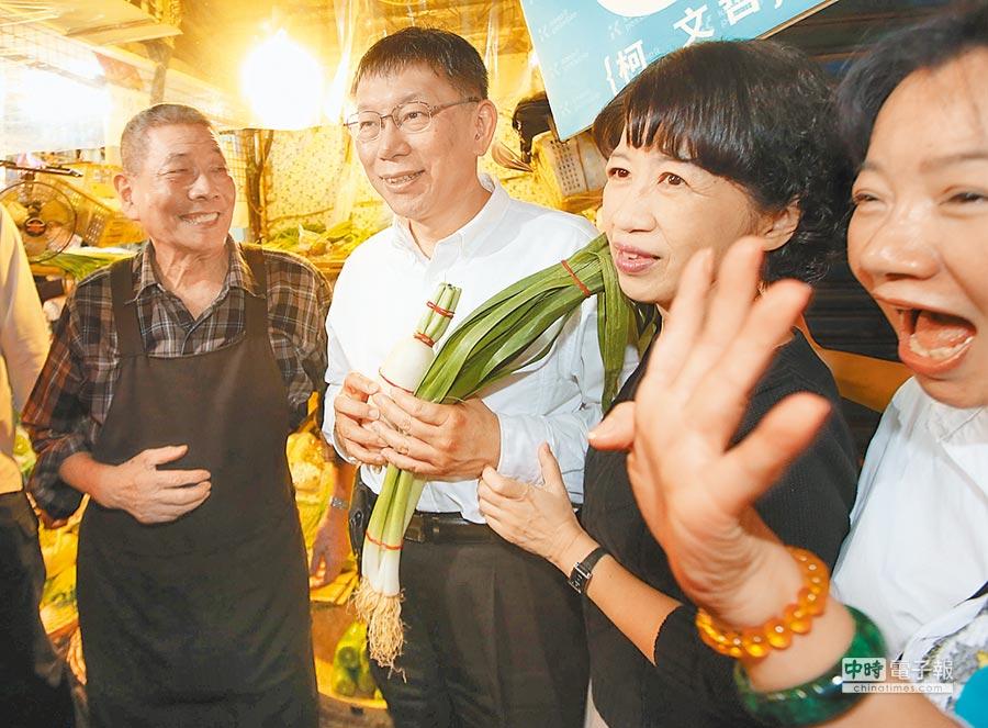 台北市長候選人柯文哲(左二)與夫人陳佩琪(右二)13日到東門市場拜票,攤商送上菜頭及蒜祝福好彩頭。(王英豪攝)