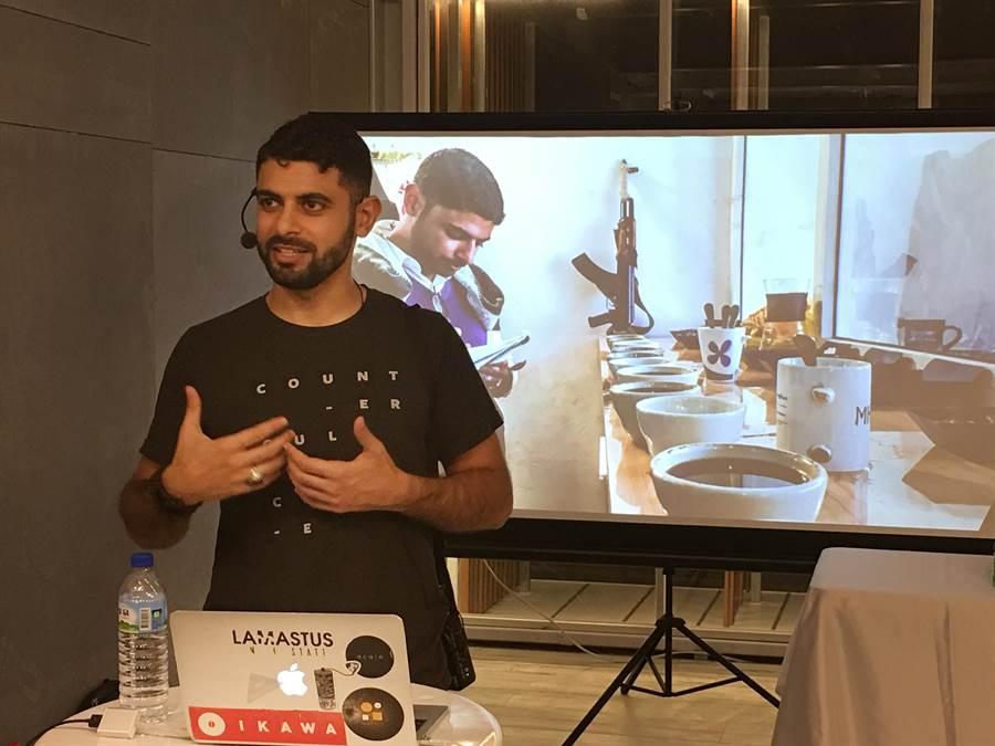 葉門飽受內戰之苦,Mokhtar Alkhanshali(莫克塔)在簡報影像中顯示,他邊作杯測,桌邊還放著衝鋒槍。(沈揮勝攝)