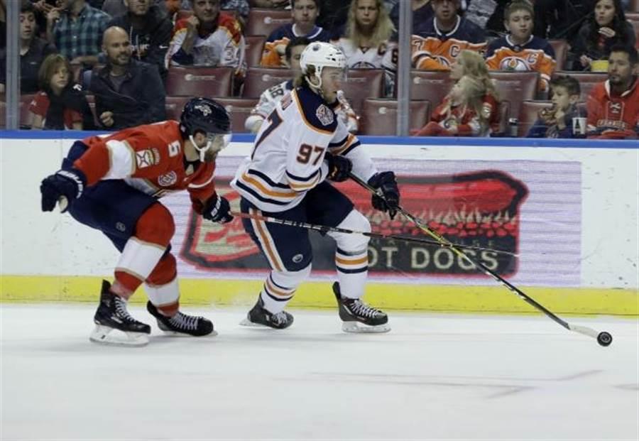 NHL油人隊麥大衛(右)持球進攻。(美聯社資料照)