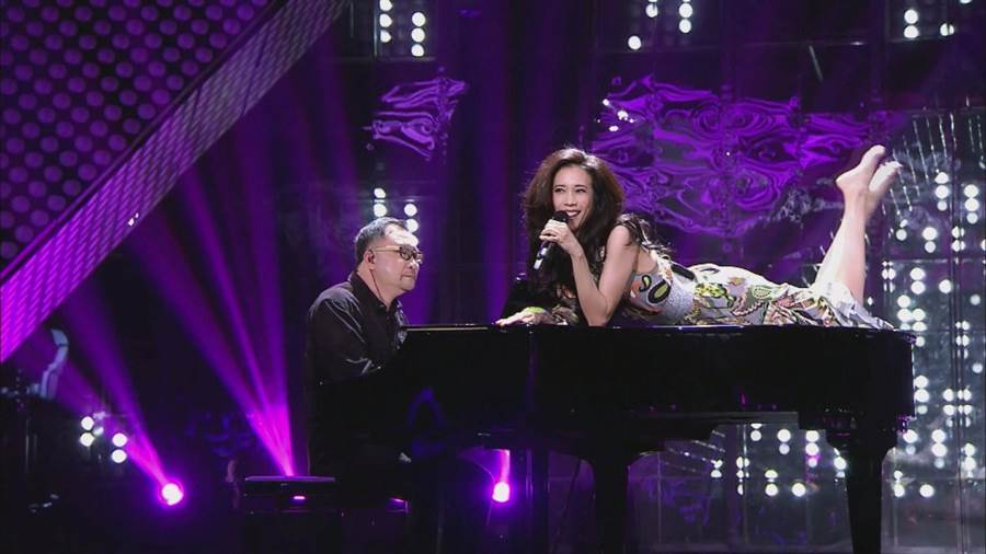 莫文蔚性感的躺在鋼琴上演唱〈有一個姑娘〉。中天提供