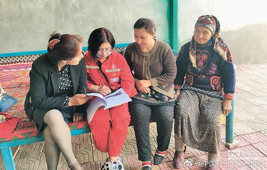 李玉英(左2)在新疆駐村工作中,與村民聊天。(取自微博@中國石化西北石油局)