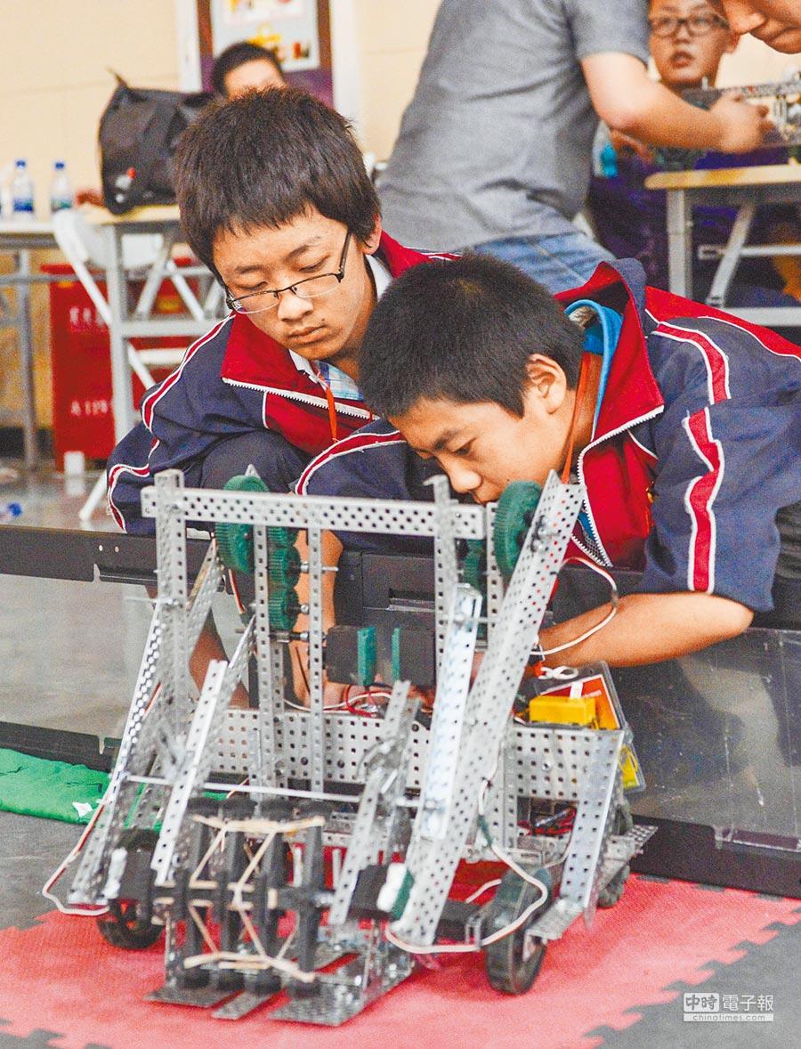 新疆阿克蘇市第四中學的學生對機器人進行調試。(新華社資料照片)