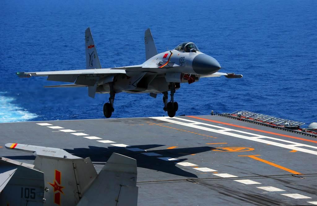 解放軍海軍遼寧艦航母編隊4月14日進行遠海實兵對抗訓練,殲-15戰機即將著艦的畫面。(中新社)