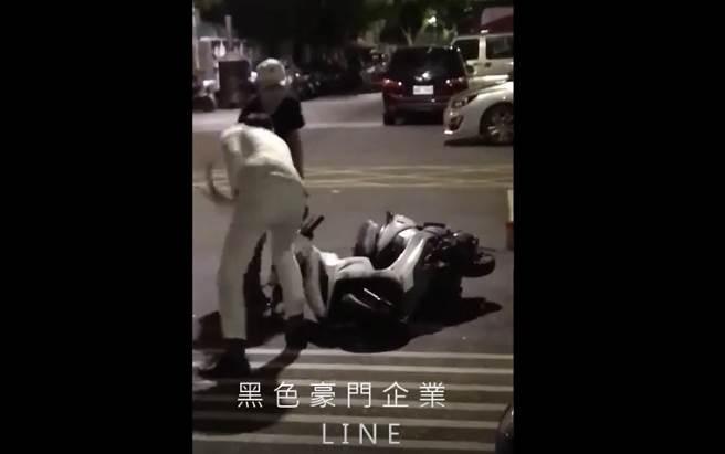 北市通河街黑白雙煞,分持榔頭、鋁棒朝一輛側躺在馬路上的機車猛砸。(李文正翻攝)