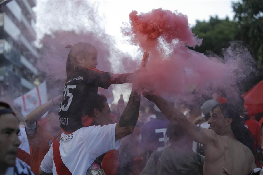 河床球迷在第2回合主場比賽攻擊波卡青年球隊巴士,圖為球迷拿煙火在場外鬧場,致使比賽延期。(美聯社)