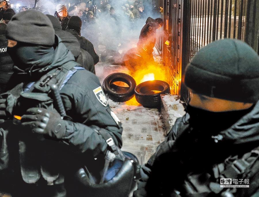 俄羅斯扣押3艘烏克蘭艦艇後,憤怒的烏克蘭民眾25日在俄駐烏大使館前聚集示威並縱火,烏克蘭士兵忙著滅火。(路透)