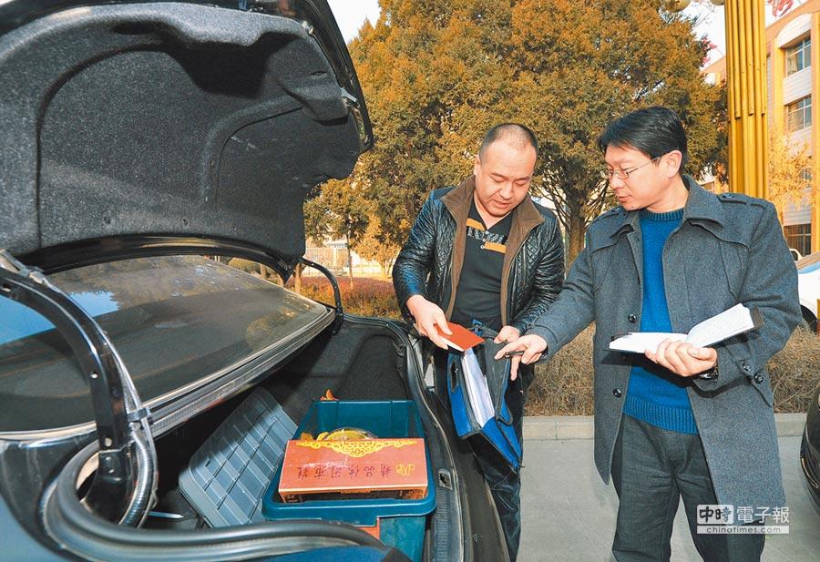 大陸紀委監察局執法人員檢查一公務車輛的車箱內,是否有收禮送禮情況。(新華社資料照片)
