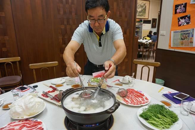 張集光示範北京涮羊肉吃法,他將生羊肉放進撈網內,以滾燙熱湯涮成粉紅色,即可入口食用。(王文吉攝)
