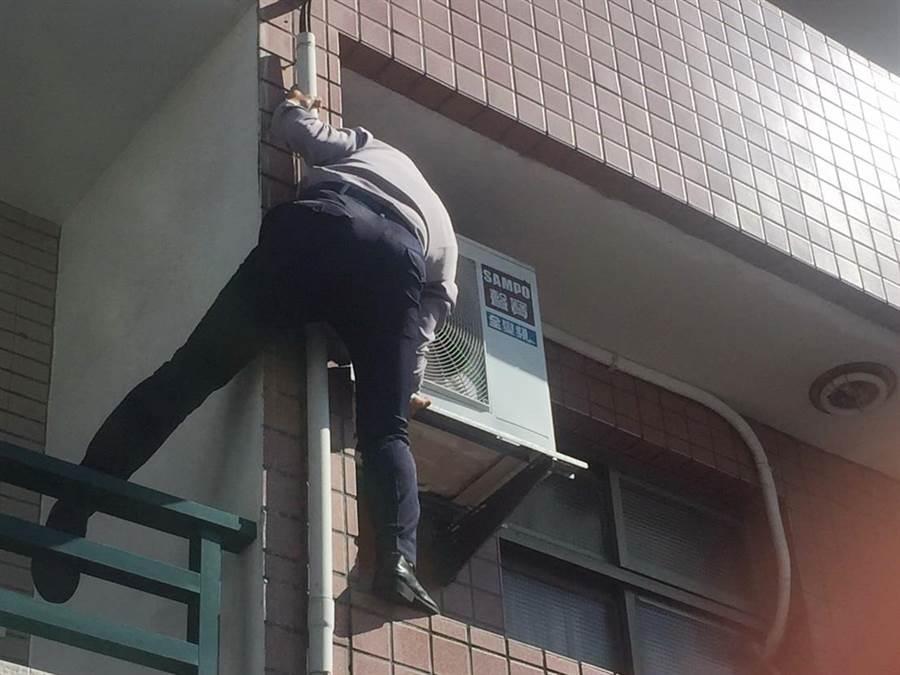 員警學蜘蛛人爬上兩樓高的鄰房,再翻牆進屋救人。(陳淑芬翻攝)