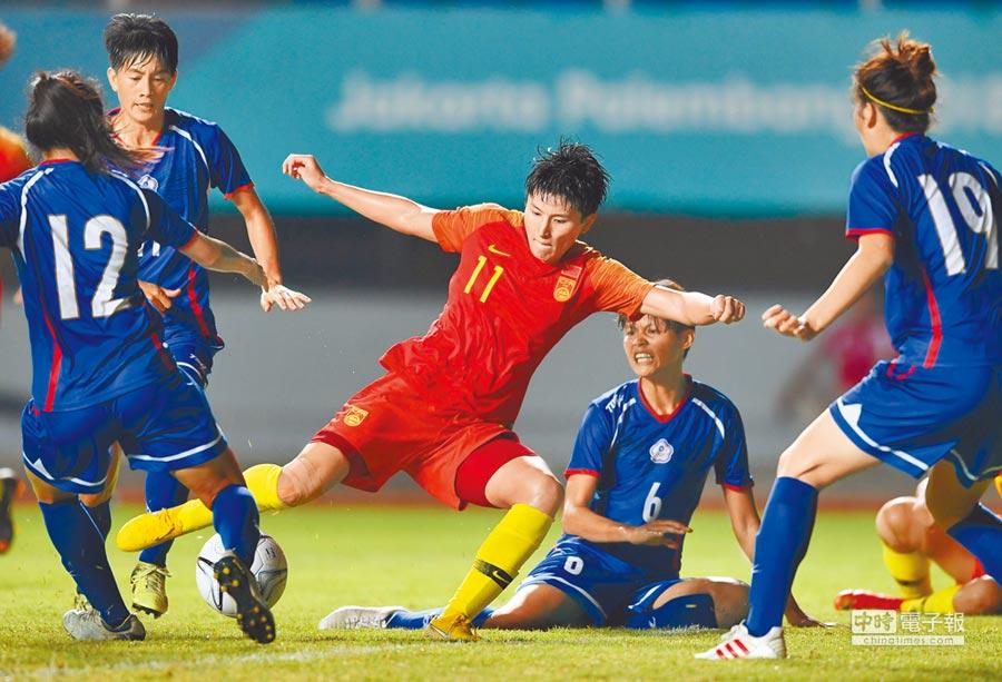 兩岸女足繼雅加達亞運後,東亞盃將再交鋒,圖為中華隊後防力阻大陸前鋒王珊珊(中)射門。(新華社資料照)