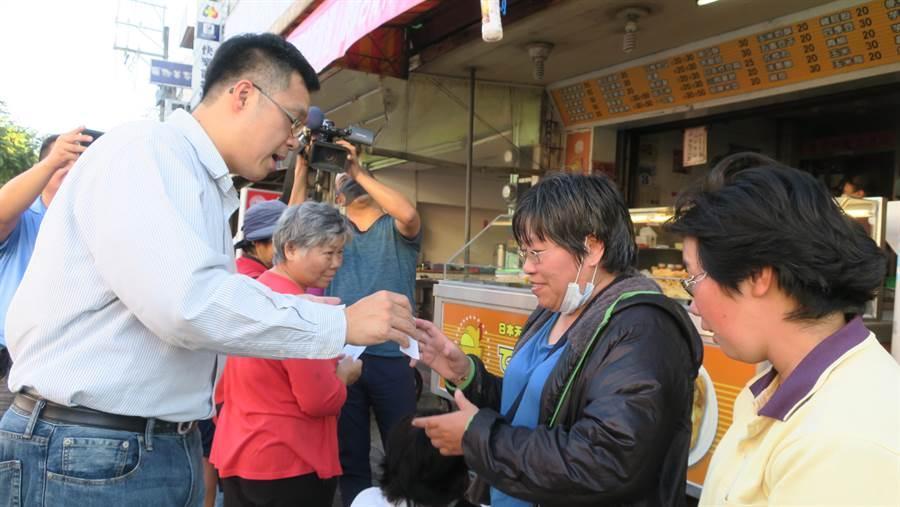 陳彥名(左)一一發出號碼牌。(謝瓊雲攝)