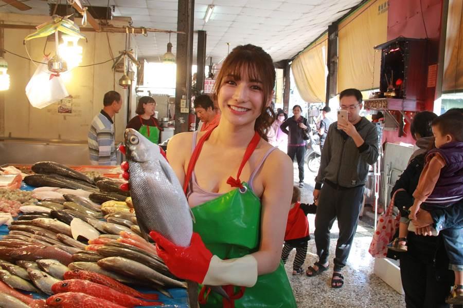 阿澎捧著殺好的新鮮烏魚,露出甜美笑容,深具模特兒架式,立刻引來一陣猛拍。(謝瓊雲攝)