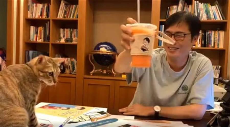 陳其邁秀出的杯袋,上頭有著他跟愛貓陳小米的照片。(翻攝陳其邁臉書直播影片)
