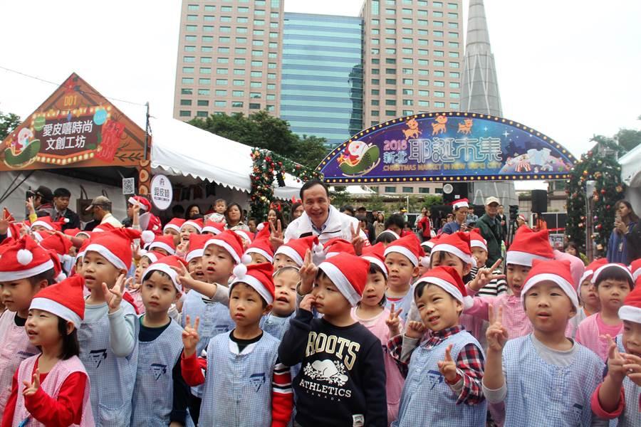 新北市長朱立倫7日上午主持2018耶誕市集開幕儀式,與幼兒園小朋友開心互動。(譚宇哲攝)