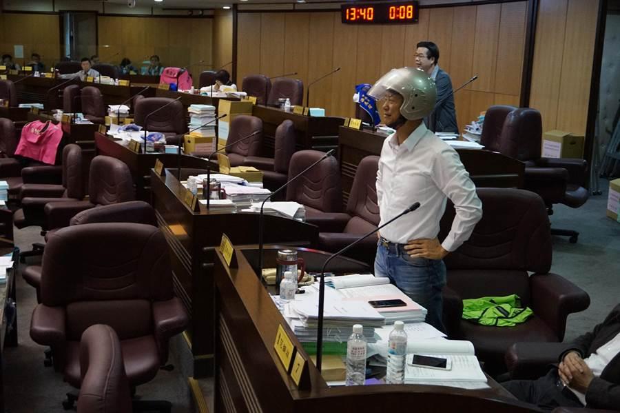 市議員蔡永芳戴上全罩式安全帽質詢,認為剪綵發生受傷純屬意外,與工程品質沒關,扯太遠了。(甘嘉雯攝)