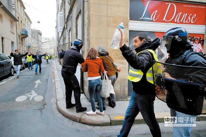 法國「黃背心」運動進入第4周。巴黎等大城市8日全都發起示威活動。圖為波爾多街頭穿黃背心的抗議者舉手就逮。(路透)