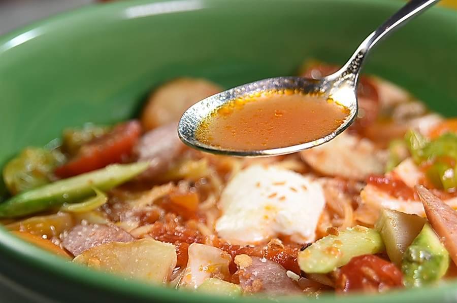 〈德腸野菜起司番茄湯麵〉的湯頭是以薩索雞骨、新鮮番茄與一點番茄糊熬製的雞湯,味道甘甜並帶有番茄酸。(圖/姚舜)
