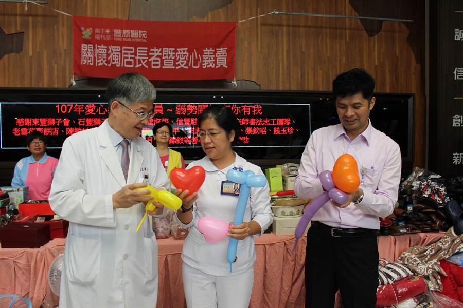 豐原醫院副院長匡勝捷(左)、秘書廖述漙(右)現學現賣,折出愛心花朵及寶劍。(王文吉攝)